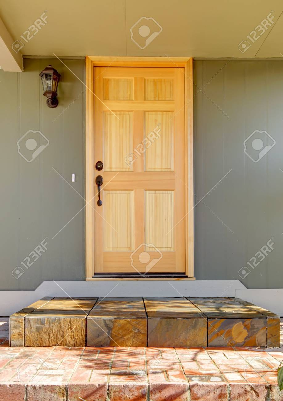 Front door light wood with green house close up and stone tiles. Stock Photo - 12760641