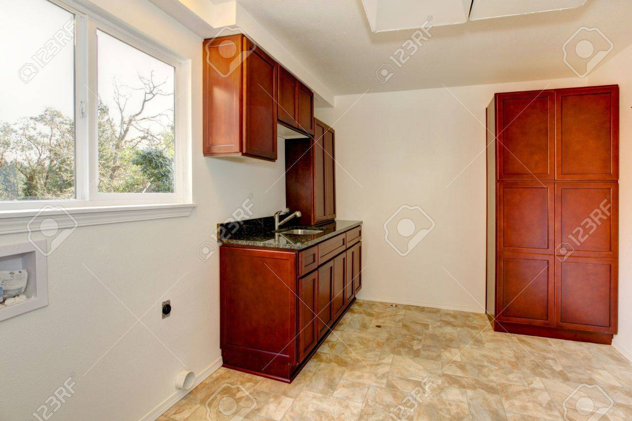 Empty laundry room interior with cherry wod cabinets. Stock Photo - 12760880