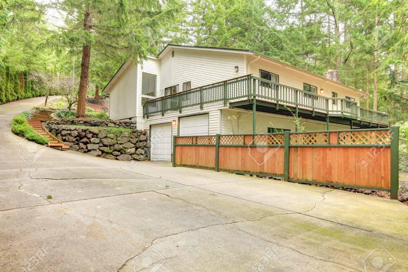Beige amerikaans huis in het bos op de heuvel met een hek en ...