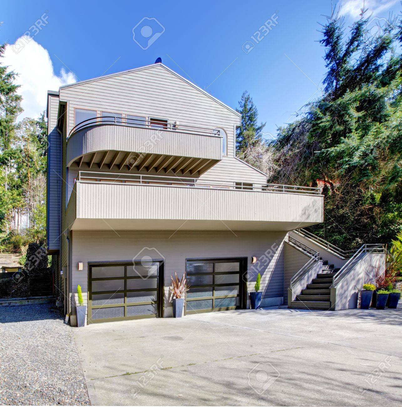 Light brown modern house exterior in spring forest with cherry blossom. Stock Photo - 13122544