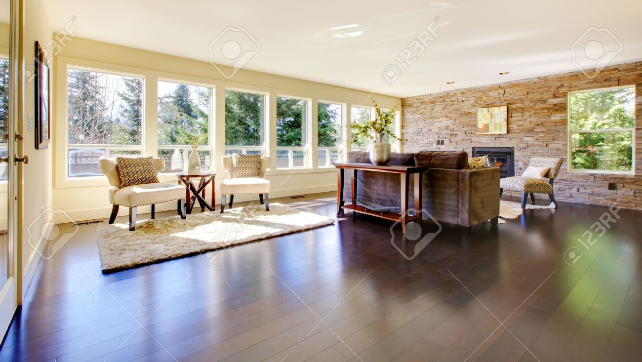 Beautiful modern large bright living room with dark floor and stone wall. Stock Photo - 13122540