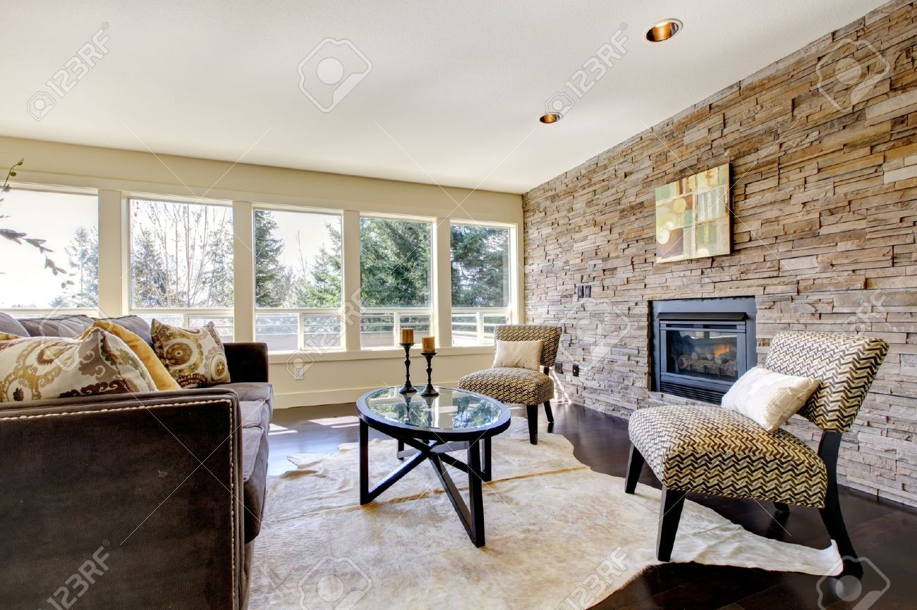 Beautiful Modern Large Bright Living Room With Dark Floor And Stone Wall.  Stock Photo