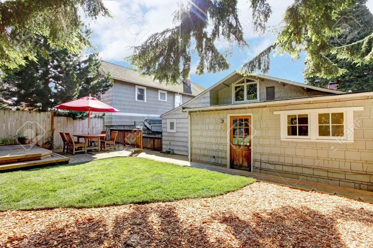 Back yard with deck and grey house and pine trees. Stock Photo - 13163678