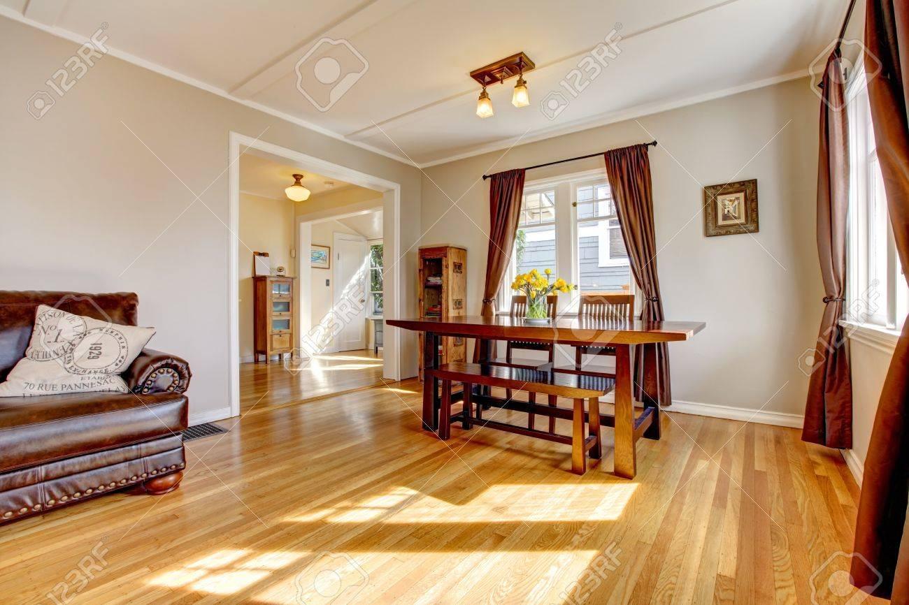 Comedor con cortina de color marrón y piso de madera y sofás de cuero.