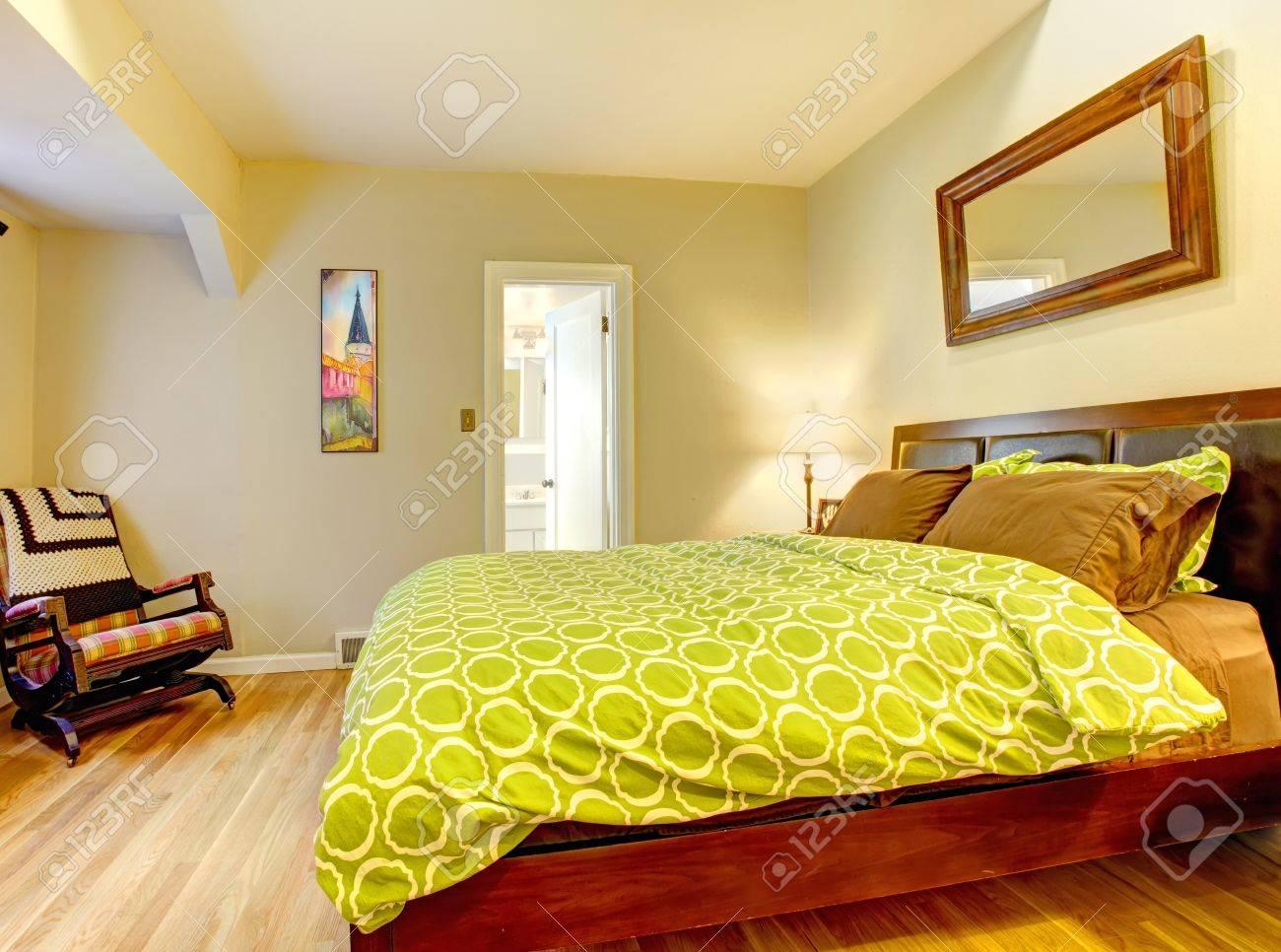 Chambre à coucher moderne avec couvre-lit vert clair et plancher de bois  franc.