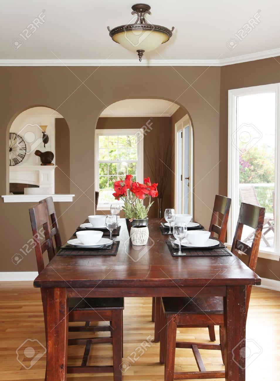 Comedor con paredes de color marrón y una mesa de madera en la casa de lujo.