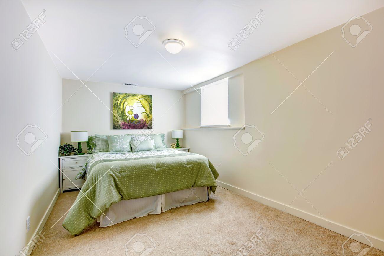 Witte grote slaapkamer met groene bed en kunst en beige tapijt ...