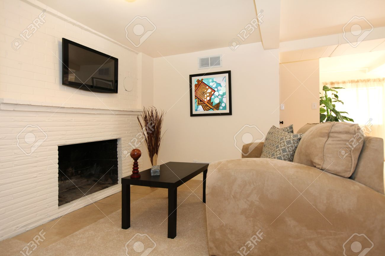 simple living room with tv and fireplace with beige sofa. stock, Living room