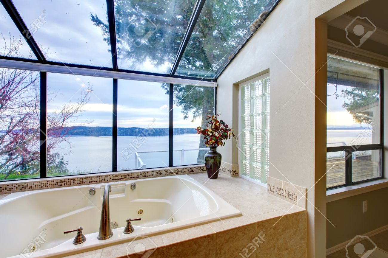 Large Tub With Beige Tiles And Glass Wall Of Windows. Stock Photo ...
