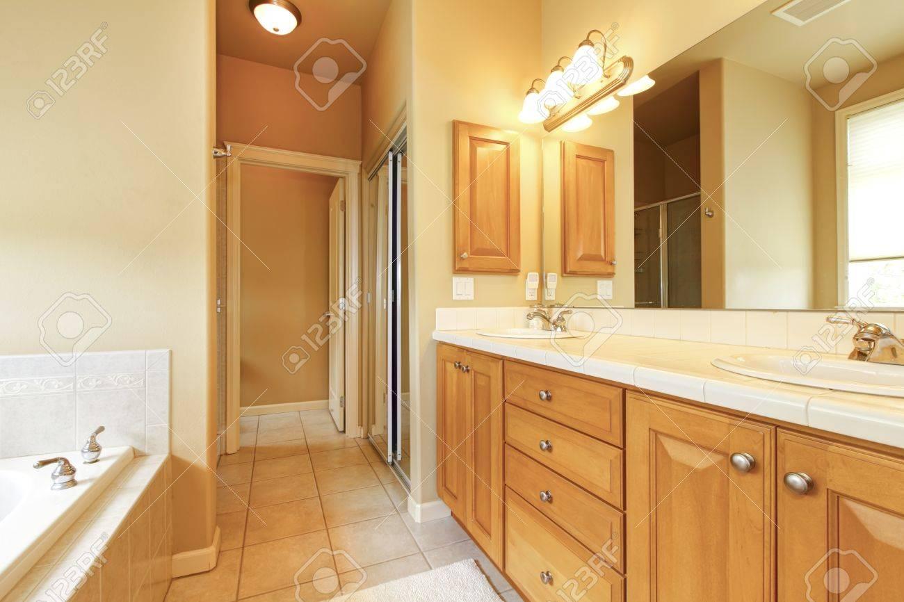 Intérieur Salle de bains avec carrelage beige et armoires en bois.