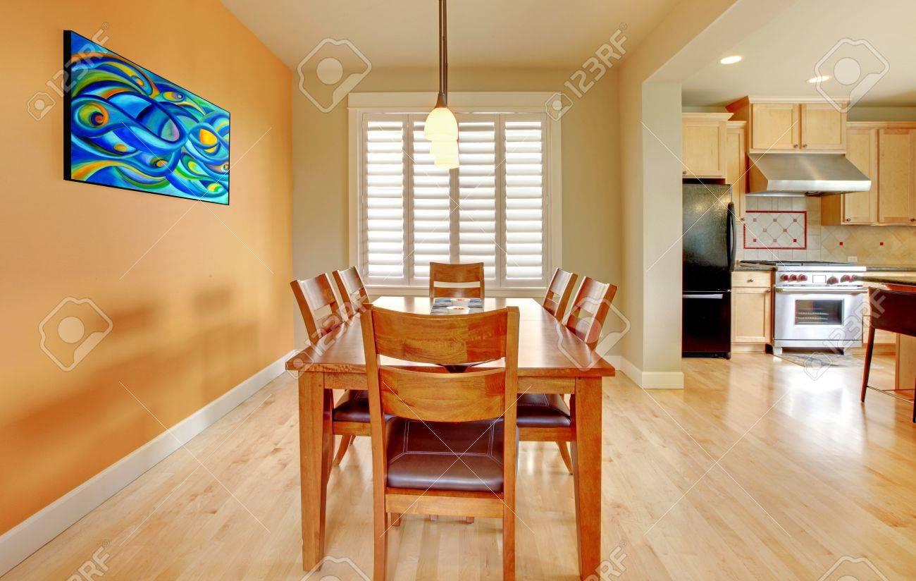 Bella sala da pranzo con pavimento in legno e cucina.