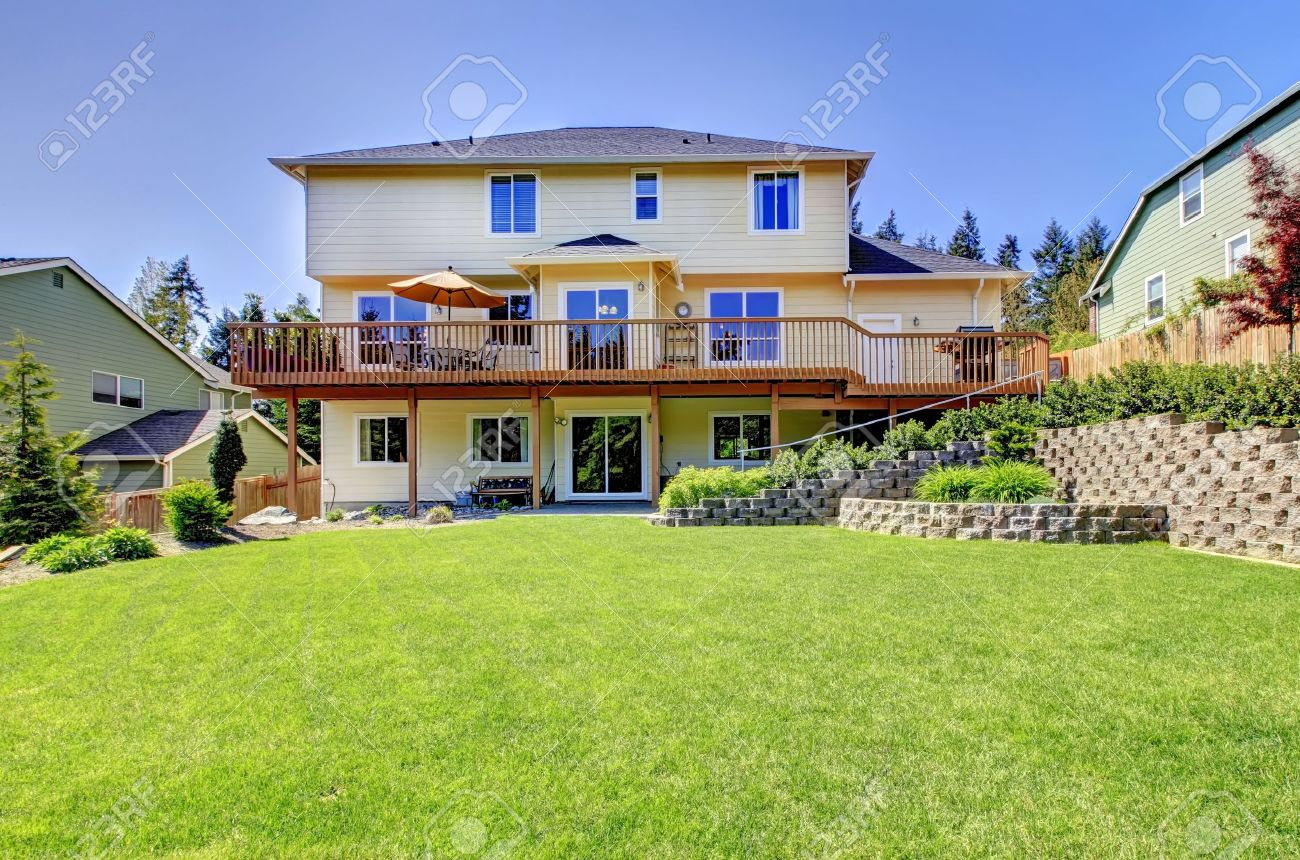 backyard of american two story house with fenced yard and simple