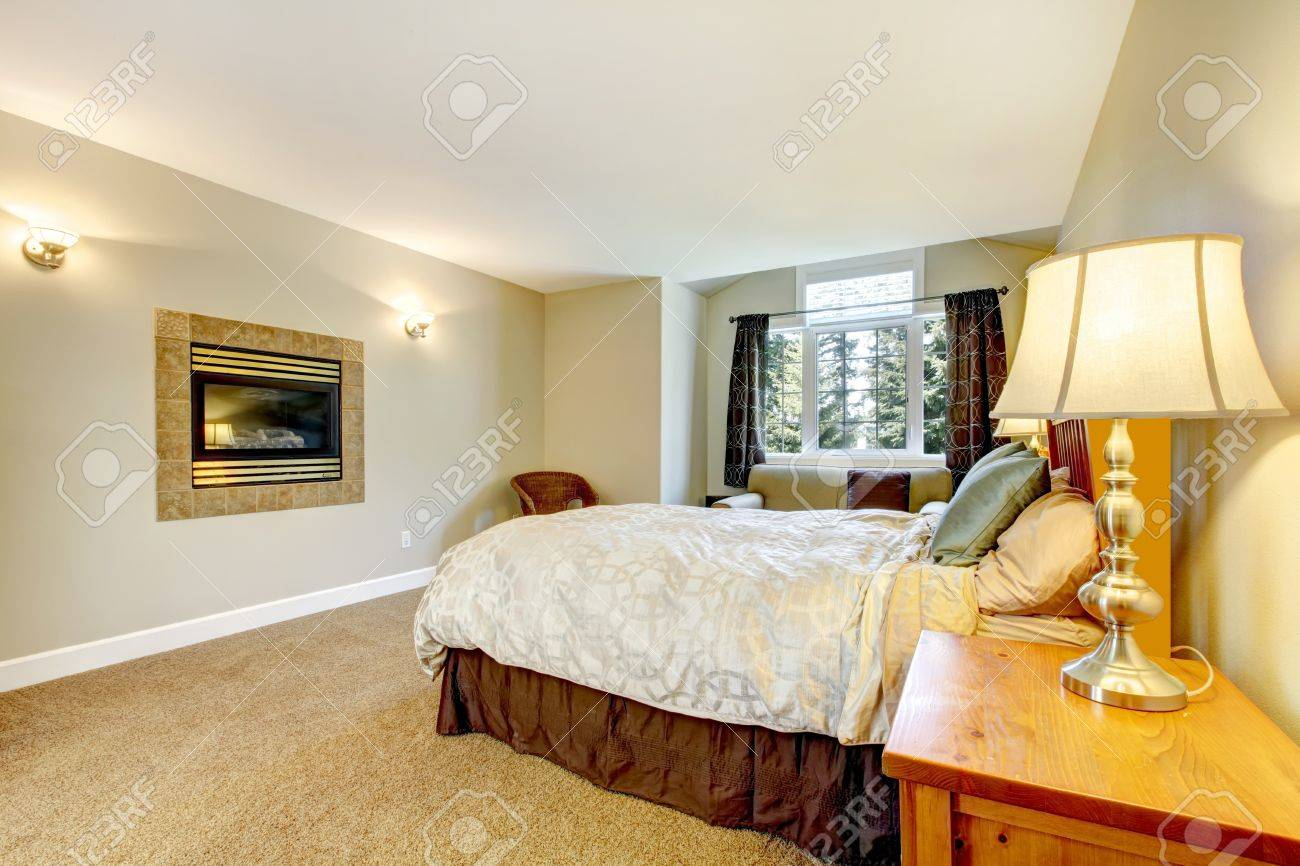 Large bedroom with fireplace and nightstand with lamp and brown carpet. Stock Photo - 14615043