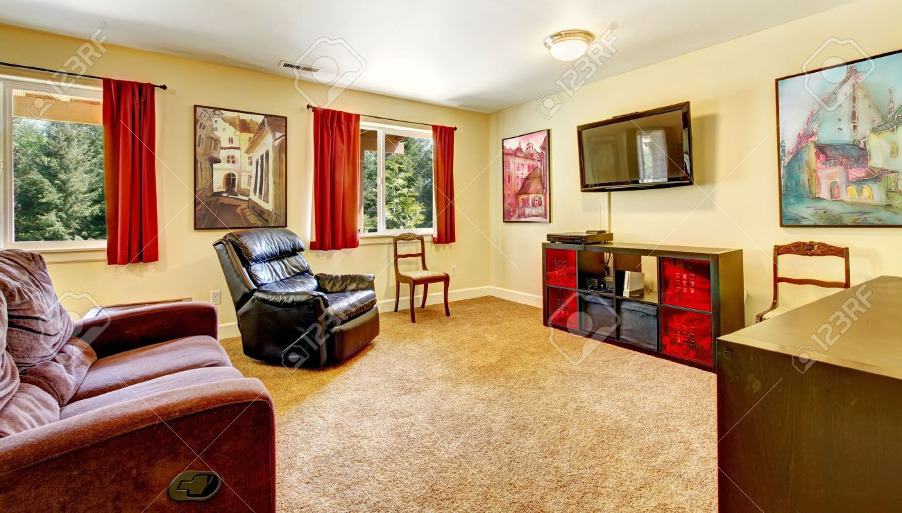 Tv living room with art and red curtains and beige carpet with brown furniture. - 14615150