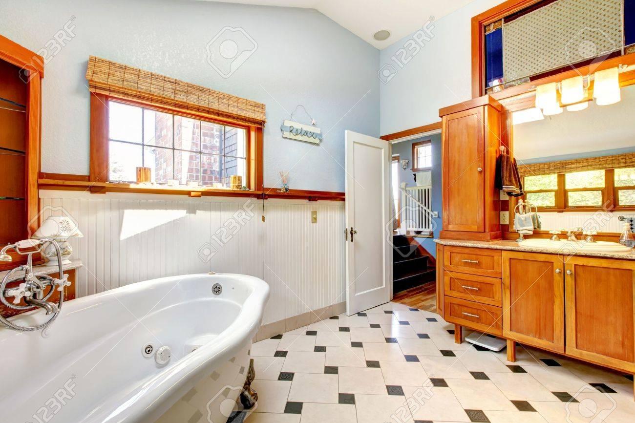 Gran cuarto de baño interior clásico azul con bañera y azulejos y muebles  de madera.