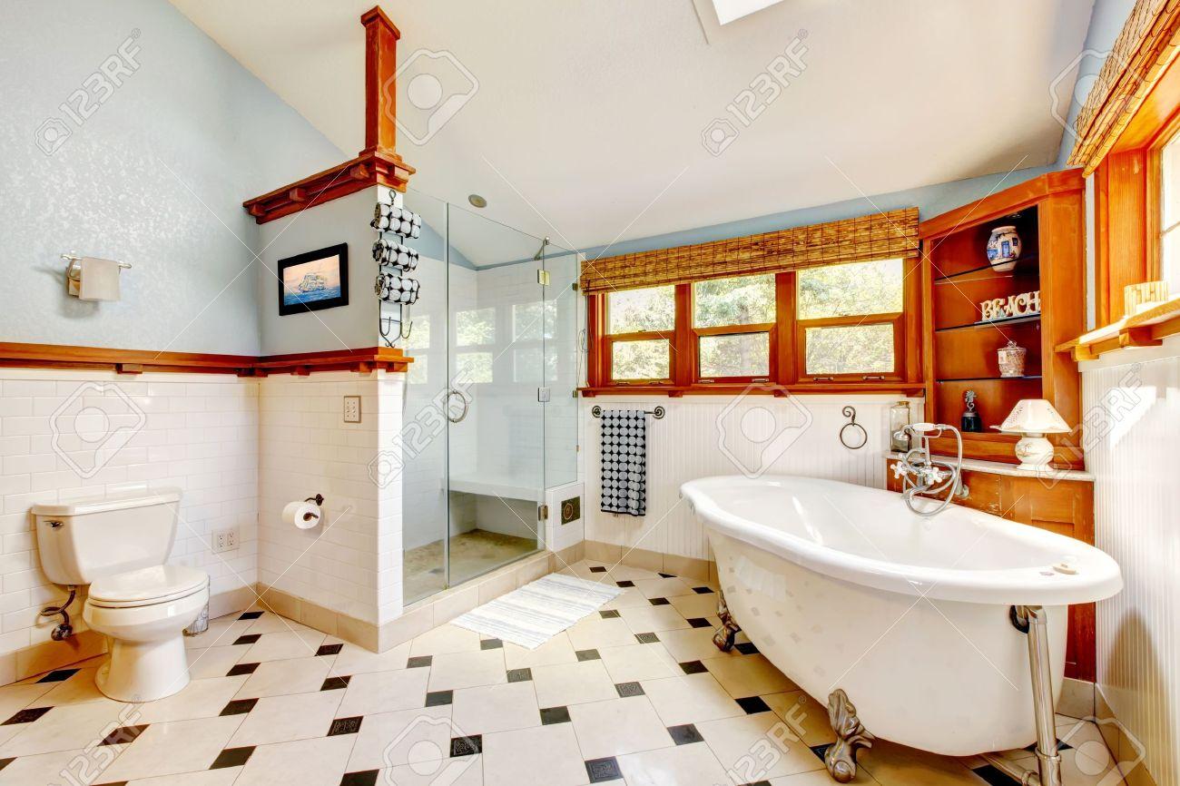 Stora klassiska blå badrum inter med badkar och kakel och trä skåp ...