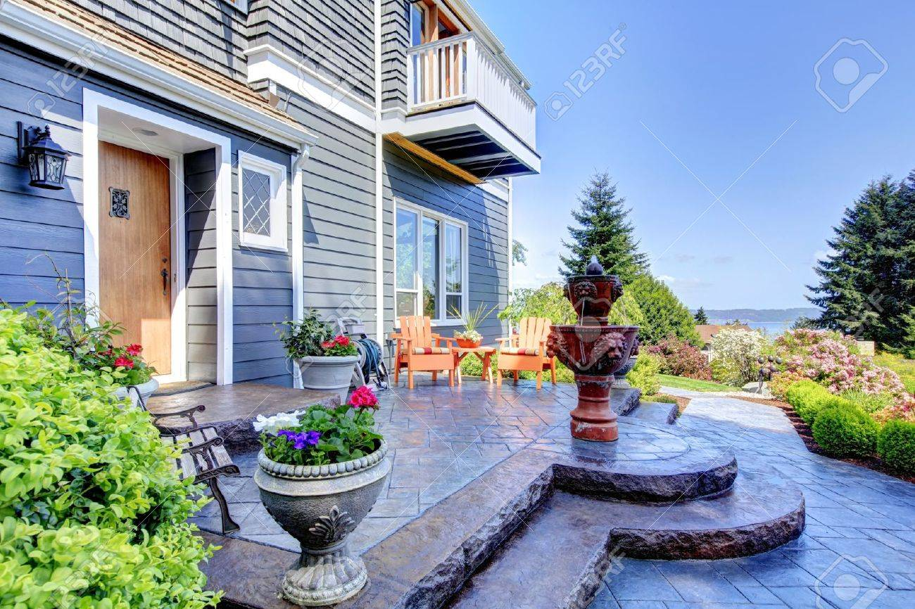 front of the blue luxury house exterior with fountain and nice landscape stock photo
