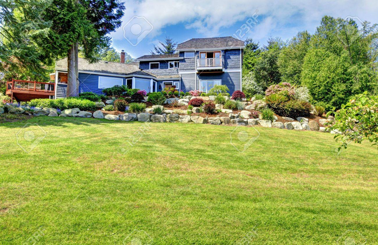 Large blue house exterior with green hill and stone walls. Stock Photo - 14615312