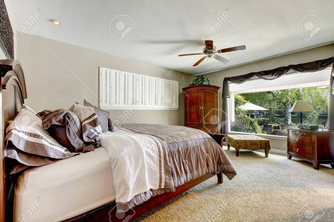 Elegant large bedroom with window and brown furniture and beige carpet. Stock Photo - 14615149