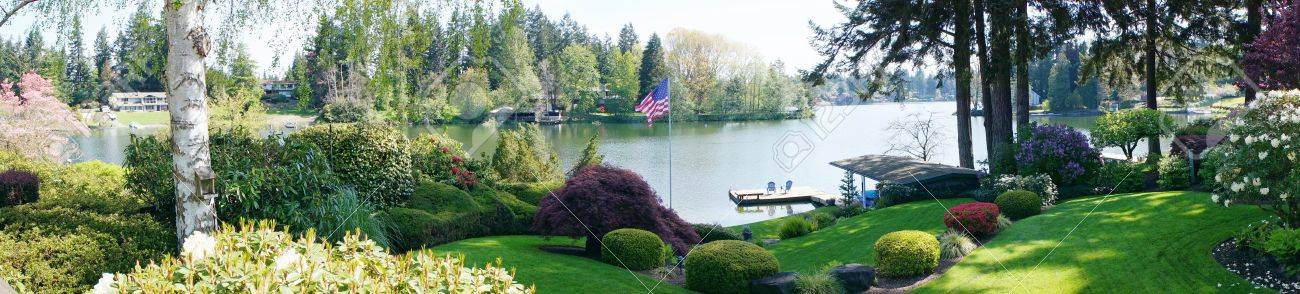 Back yard landscape with spring blooming flowers and lake and American flag. Stock Photo - 14615273