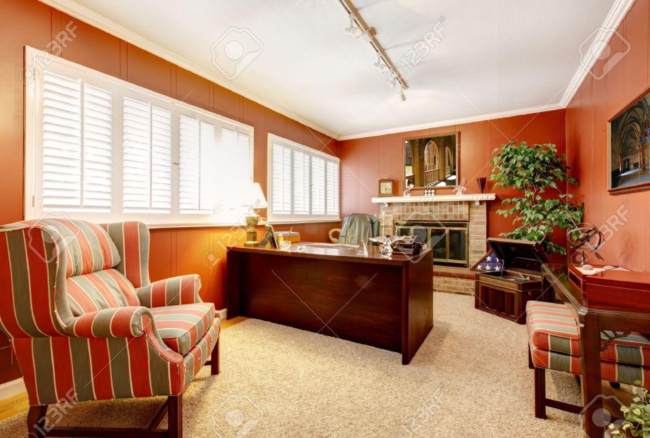 Bureau à domicile intérieur avec des murs rouges et dune cheminée
