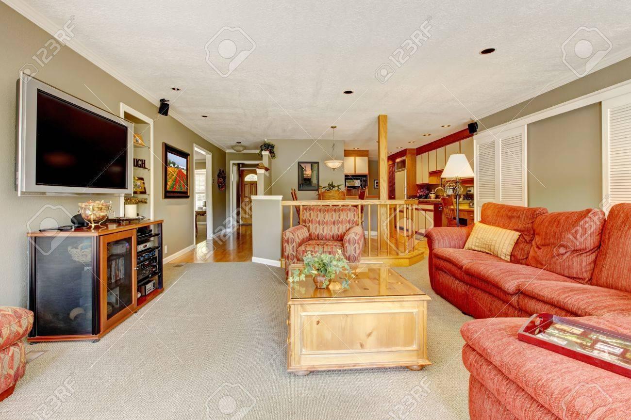 Grand salon avec canapé rouge américaine, TV et moquette beige.