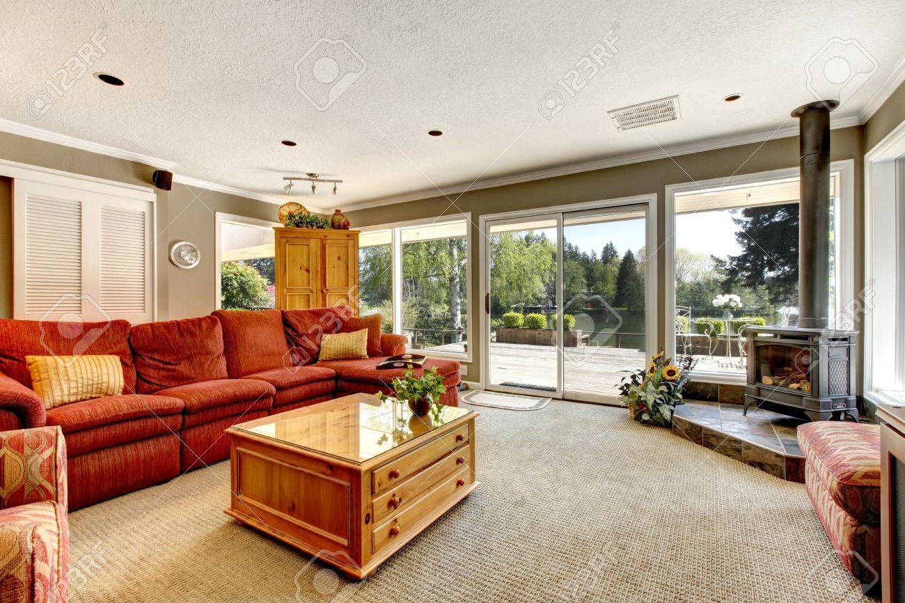 Vardagsrum med många fönster, röd soffa och spis. royalty fria ...