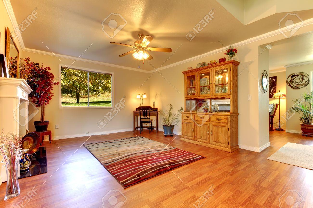 Grote woonkamer met houten vloer, rood tapijt en beige muren ...
