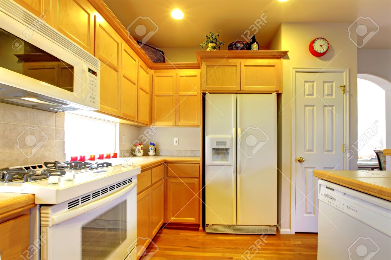 Kitchen with yellow wood cabinets and white appliances and hardwood floors. Stock Photo - 15783862