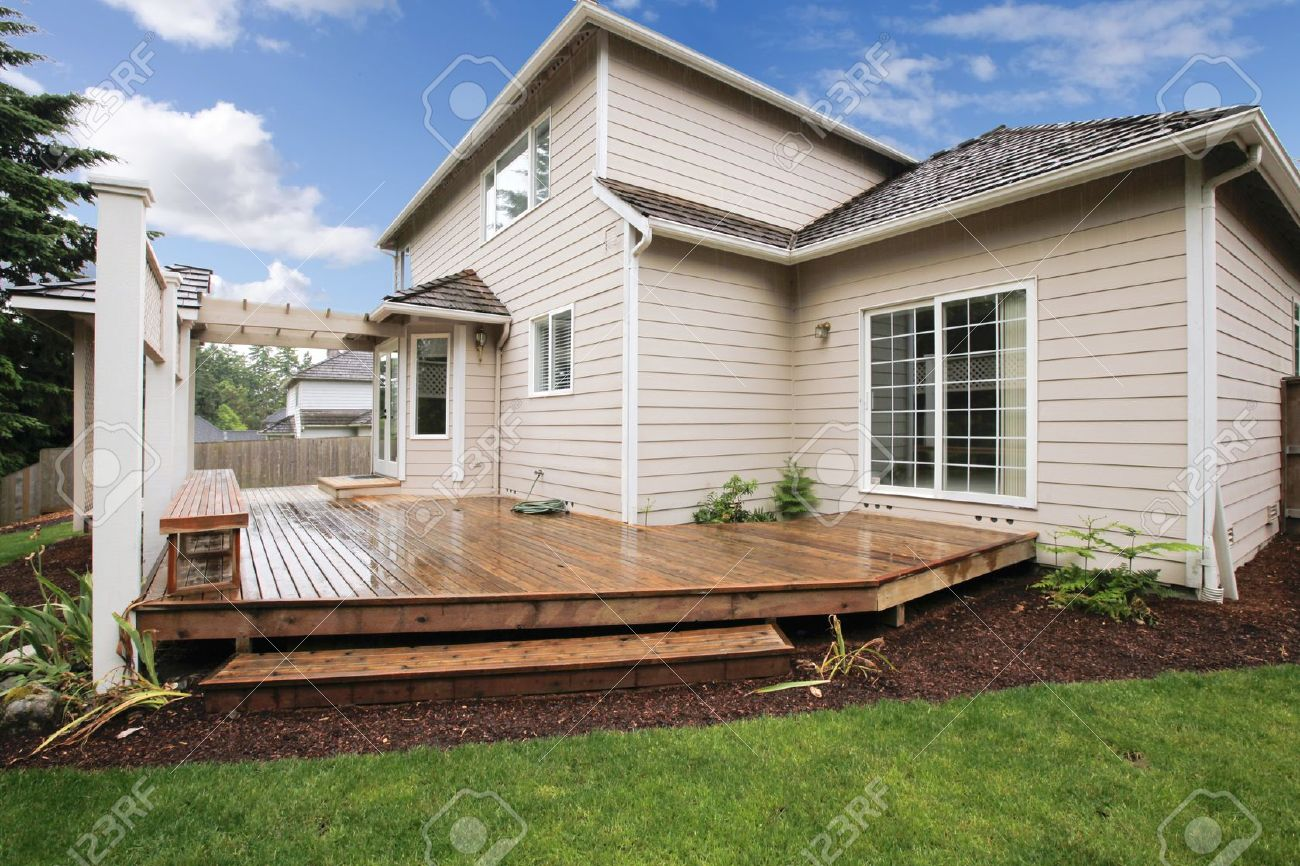 large beige house with porch from the backyard with grass and