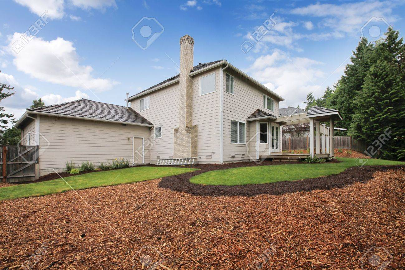 large beige house with empty backyard during spring with mulch