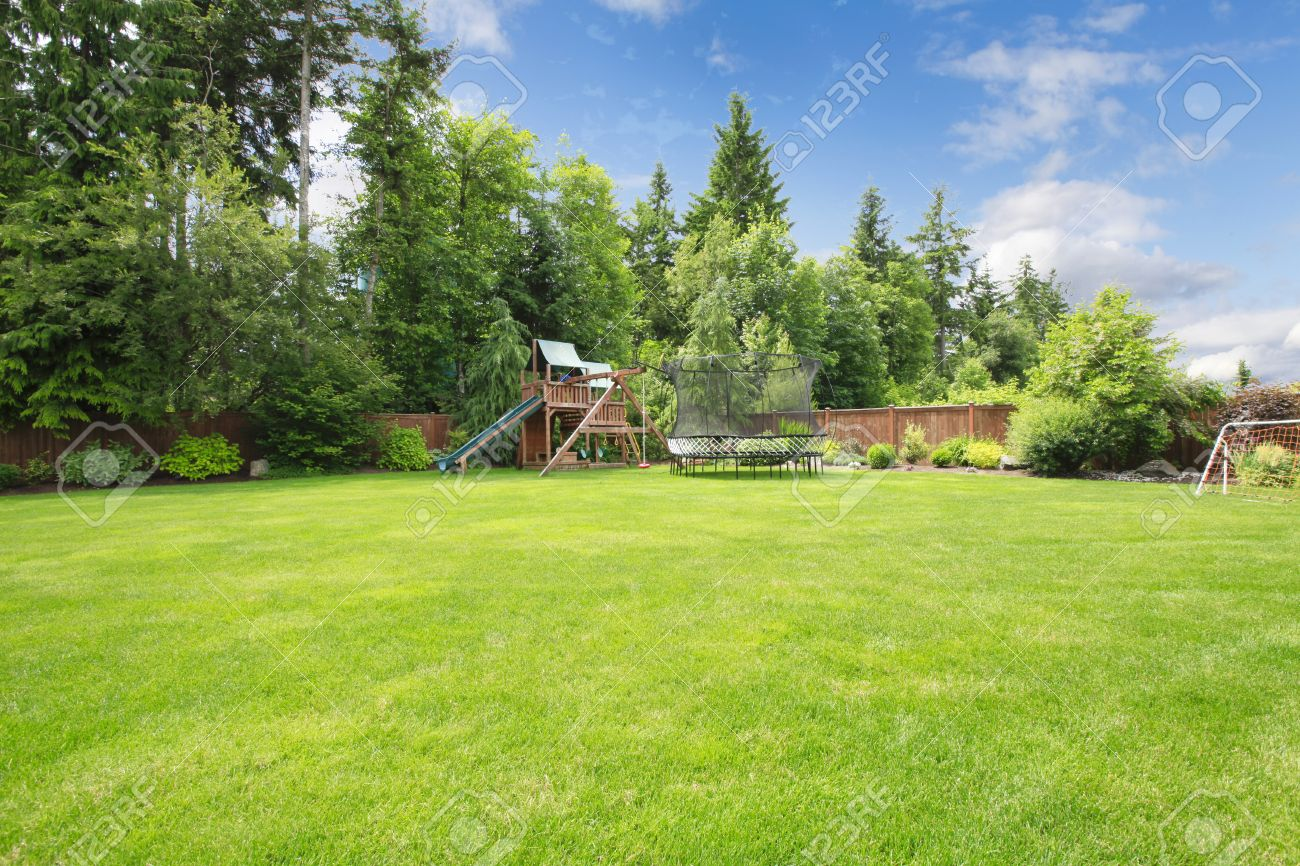 Stock Photo   Summer Fenced Backyard With Play Ground Area And Trees And  Large Lawn.