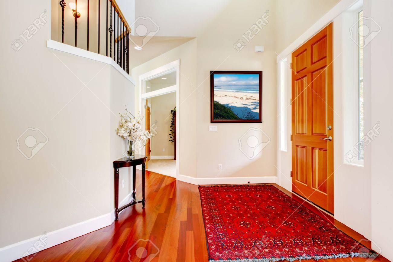 赤いラグや木製のドアが付いている大型の家高級入口 ロイヤリティー