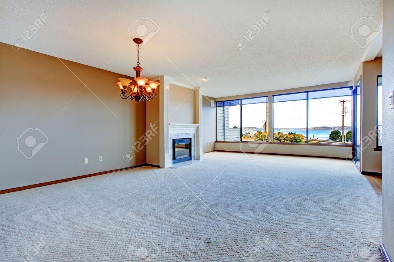 Appartement woonkamer met grote ramen, tapijt en hardhouten vloer ...