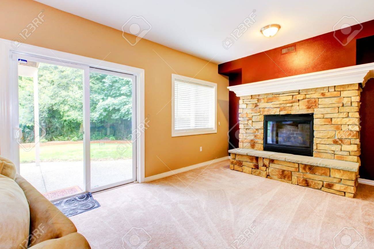 Empty yellow and red Living room with large fireplace and door to backyard Stock Photo - 16335349