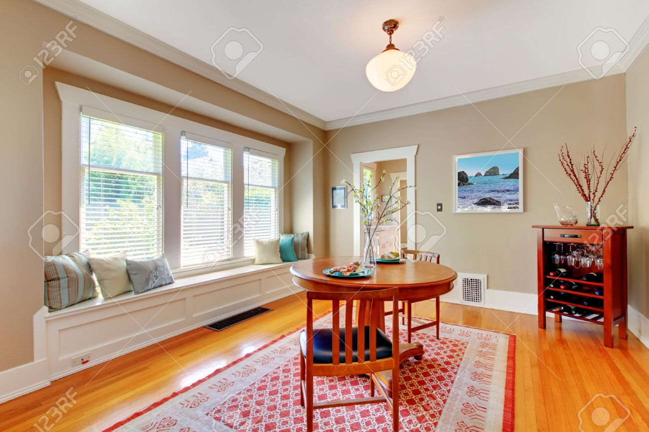 Elegant Dining Room With Window Bench Cherry Hardwood Floor And Folk Rug Stock Photo
