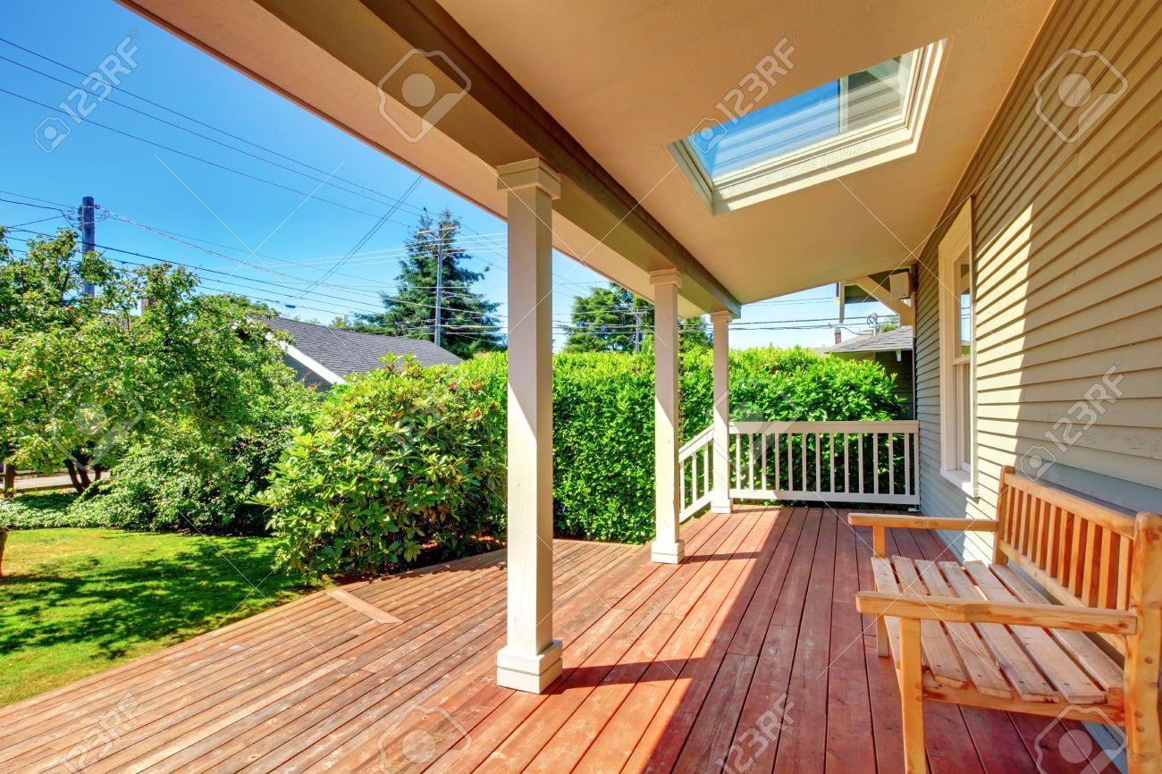 Grande terrasse couverte avec banc en bois et puits de lumière et plancher  avec paysage d\'été.