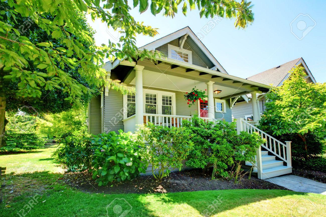 Gris petite maison avec véranda et balustrades blanches avec paysage d\'été.