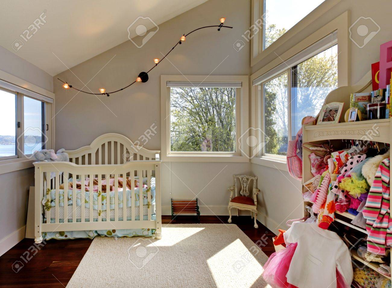 Baby girl room with white crib and clothes with many windows. Stock Photo - 16752360