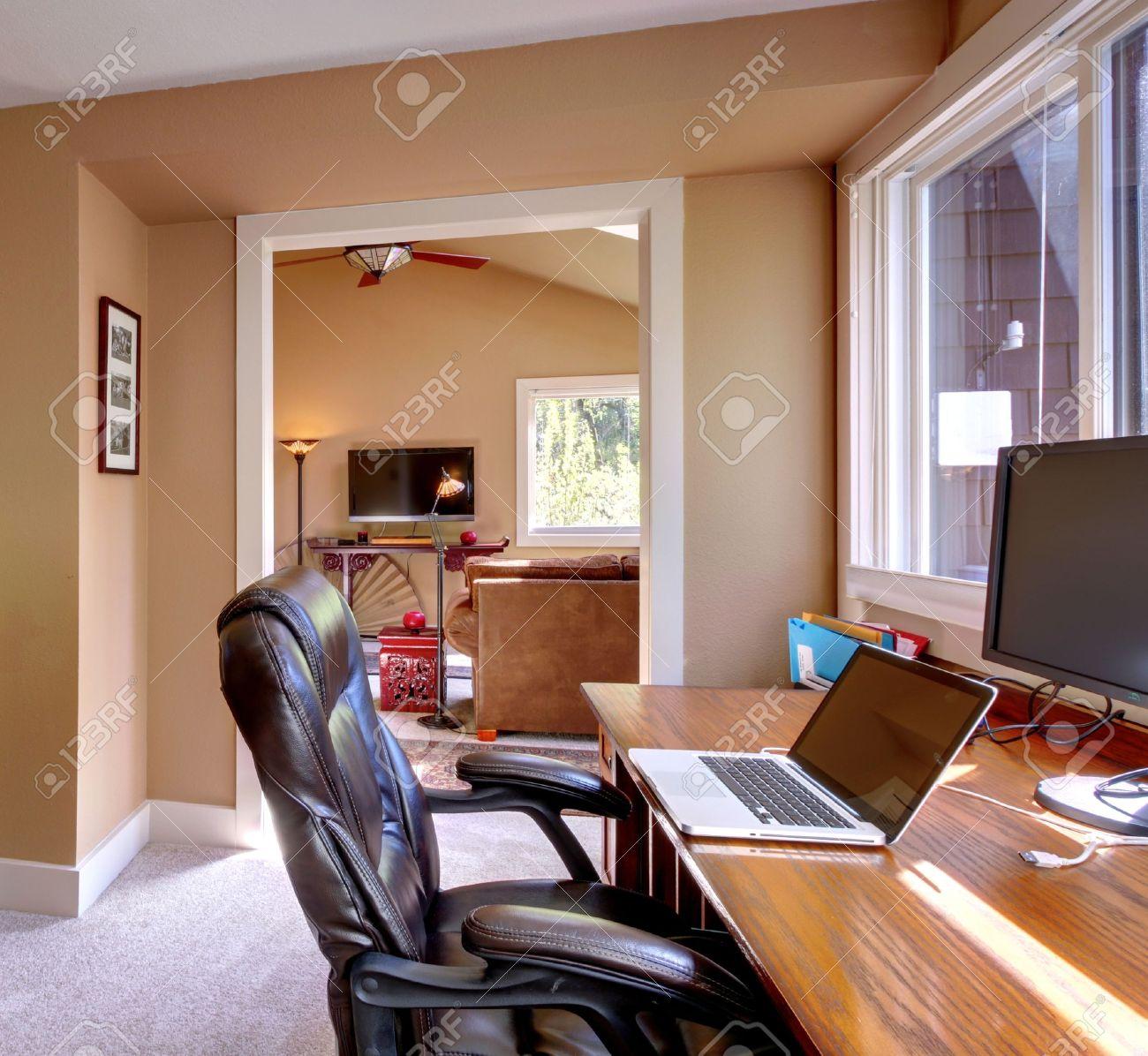 Home office en computer en stoel met bruine muren en een tv in de ...