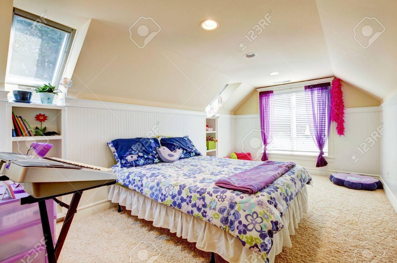 Meisje slaapkamer met zolder gewelfd plafond en beige tapijt met ...