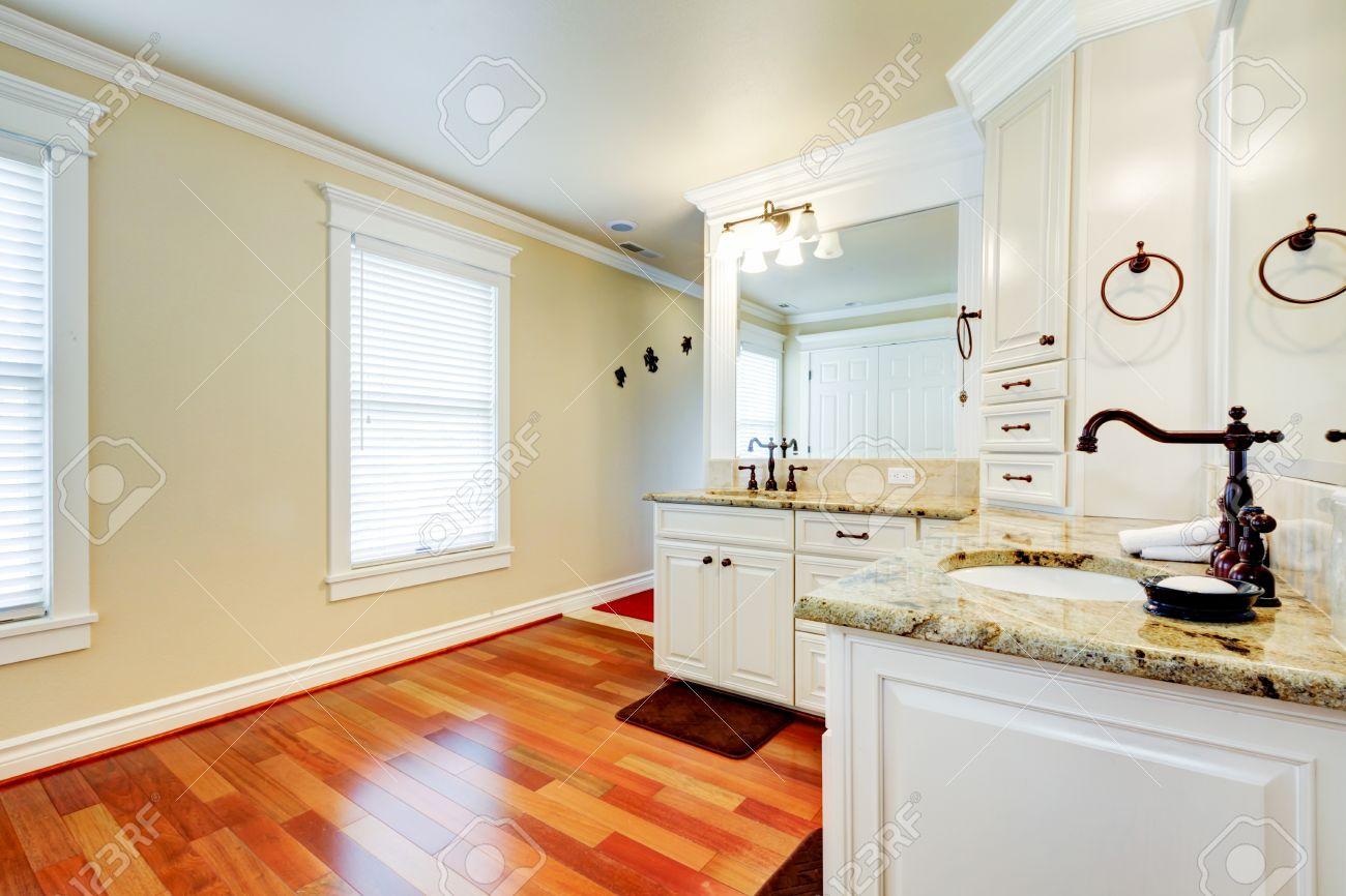 Grande salle de bains de luxe maître blanc avec du bois dur de cerise et de  lavabos doubles coin.