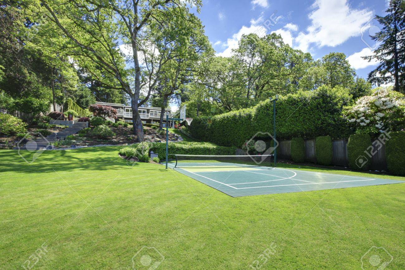 tennis court with house on the hill and bright green grass stock