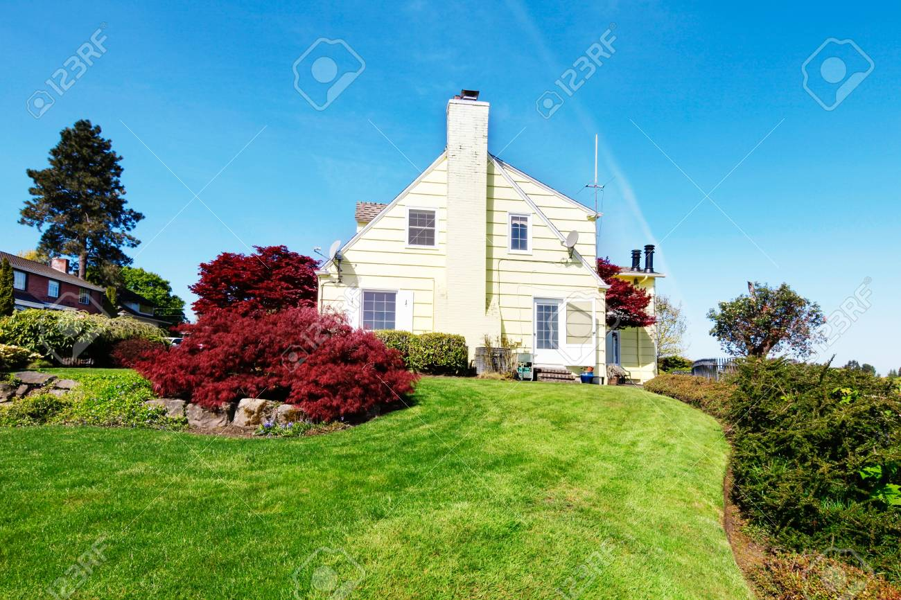 Yellow small home with water view and red maple. Stock Photo - 17124882