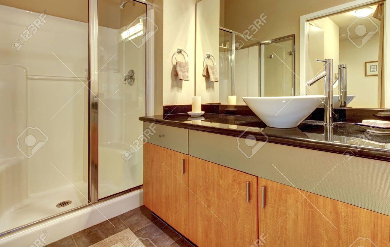 Salle de bains avec armoires en bois modernes, une douche et un évier en  verre blanc.