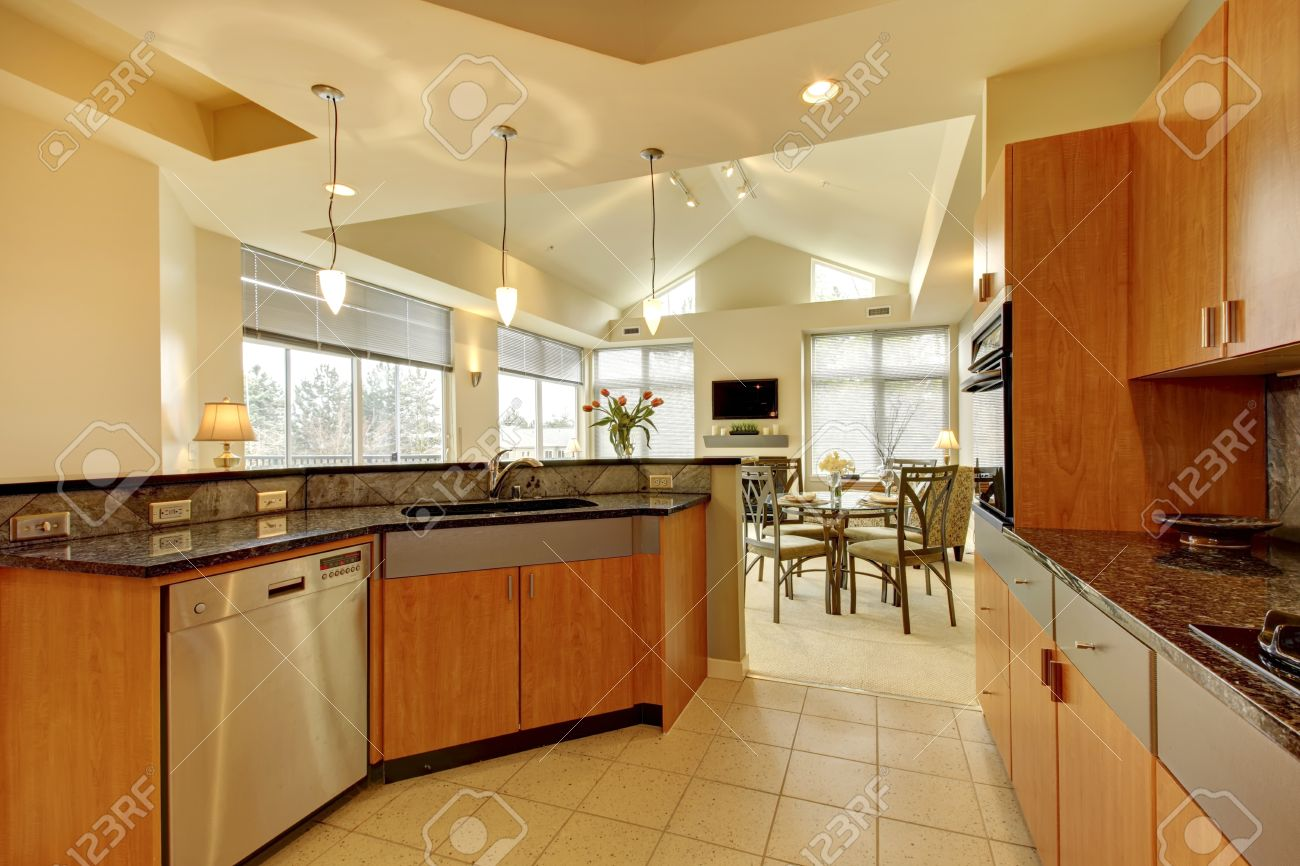 large modern wood kitchen with living room and high ceiling and