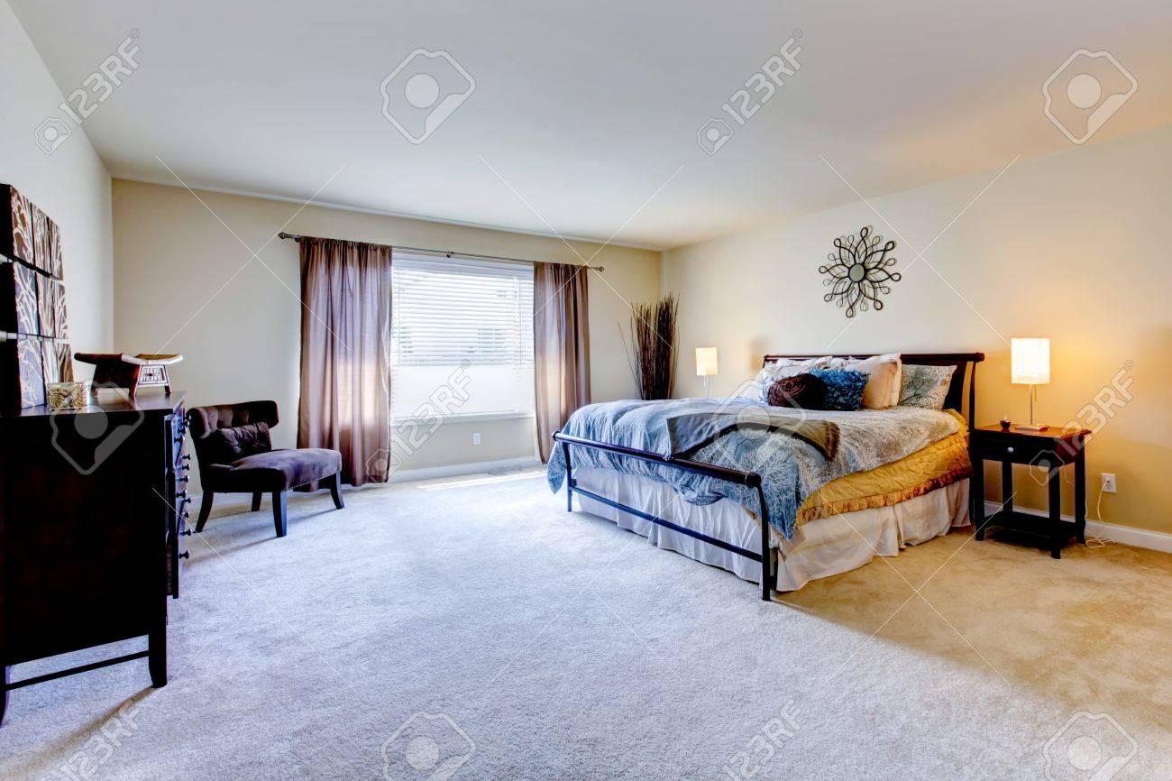Intérieur grande chambre avec moquette beige et noir lit.