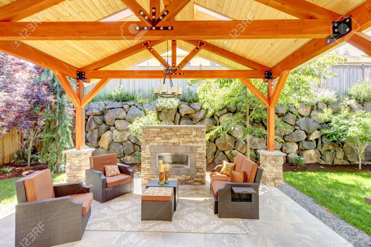 Extérieur terrasse couverte avec cheminée et meubles. Plafond en bois avec  puits de lumière.