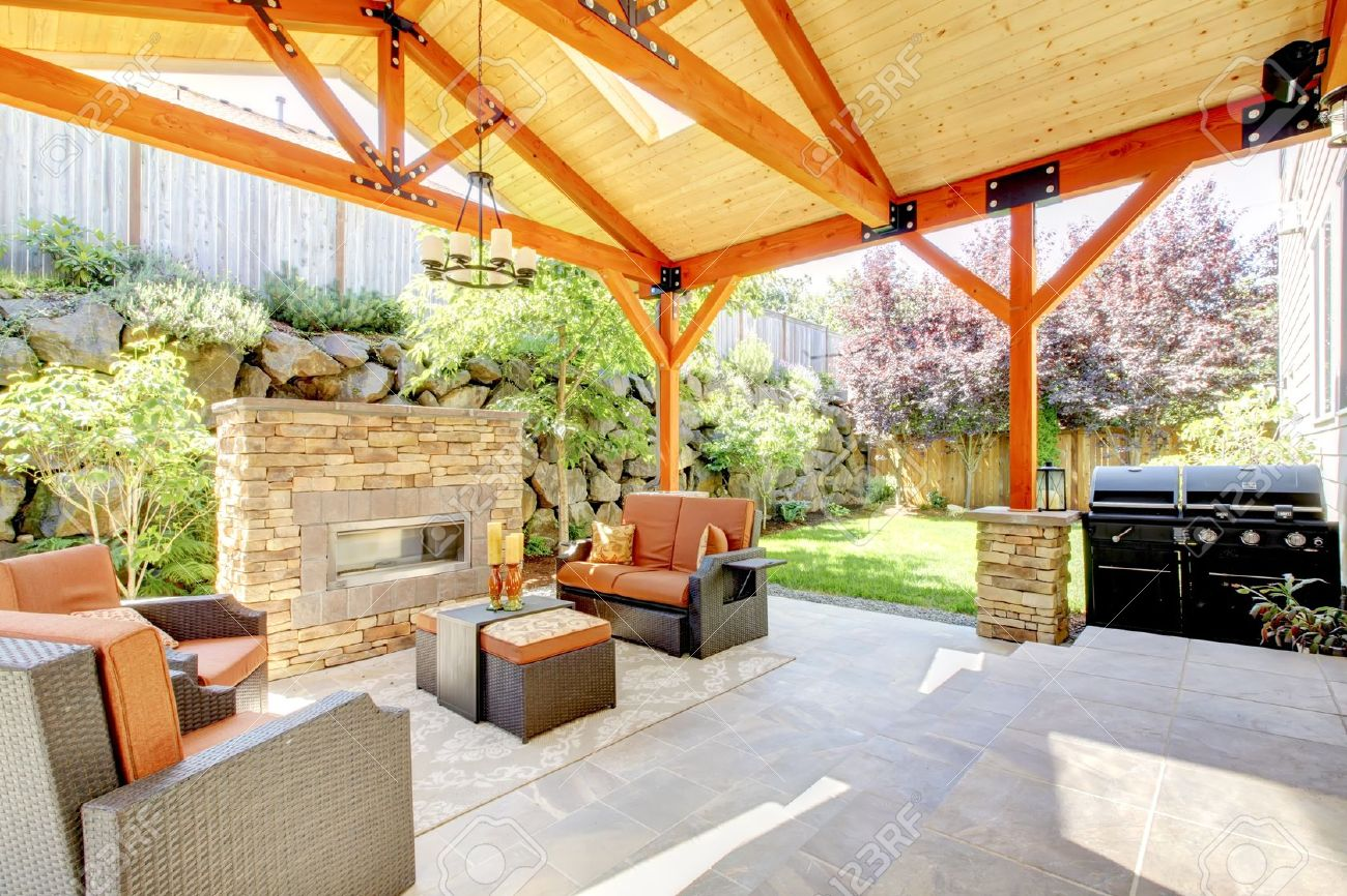 Exterior Covered Patio With Fireplace And Furniture. Wood Ceiling With  Skylights. Stock Photo
