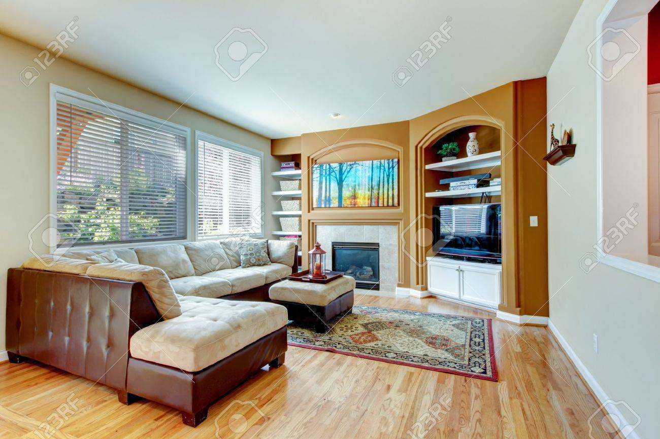 Living room with fireplace and hardwood floor, leather sofa. Stock Photo - 17749880